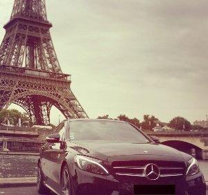macchina mercedes in primo ppiano con lo sfondo della Tour Eiffel di Parigi.